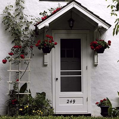 You don't have to have a fortune!  This bracketed gable overhang provides a perfect place to hang plants. A simple trellis with climbing roses to add color and interest to an otherwise plain door.