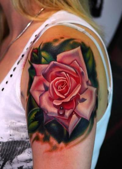 A gorgeous pink rose tattoo decorates this girl's shoulder.