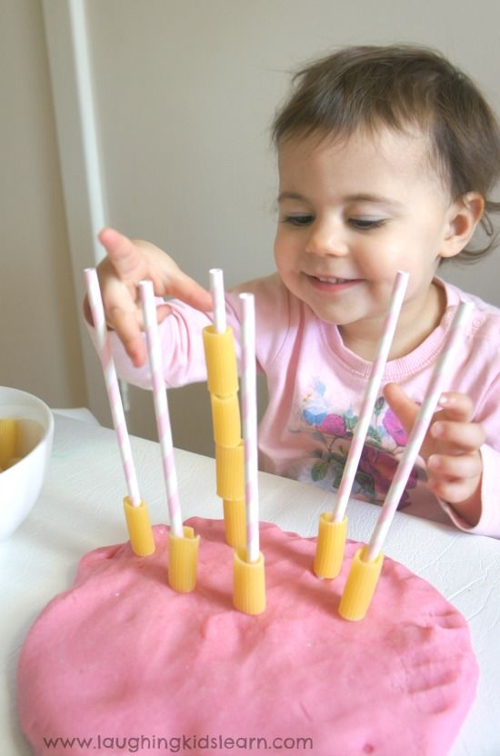 Threading pasta onto straws for fine motor skill development