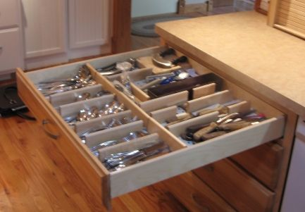 "Extra deep lower cabinets allow extra long drawers.  This one, nearly 30"" long, is fitted with dividers inserted in a pegboard bottom.  The pegs allow the drawer to be easily reconfigured when storage needs change. The long drawer allows for two rows of silverware storage front to back — compared to the normal one row (and a little) in an typical drawer — and every inch of it is immediately reachable thanks to our full-extension, soft close, hidden drawer supports."
