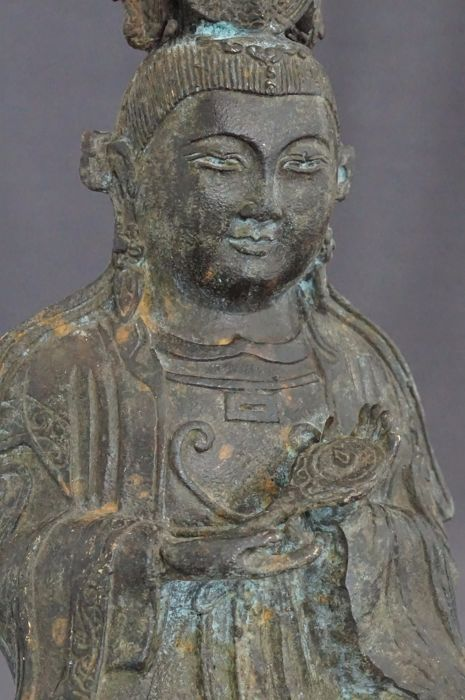 Grote bronzen sculptuur van Guanyin met spiegel met oog - China - Tweede helft 20ste eeuw  Een bronzen sculptuur van gezeten Guanyin op dubbele lotustroon met lang gewaad en in het haar 3 vogels. In haar hand heeft ze een handspiegel met daarin het oog. Conditie: De sculptuur verkeert in uitmuntende conditie met mooie patina.Hoogte: 162 cm.Verzendmethode: Het kavel wordt zorgvuldig verpakt en verzekerd verzonden via PostNL. Indien u meerdere van mijn kavels in deze veiling koopt betaalt u…