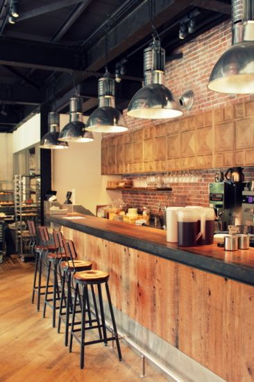 This cafe feels light and airy. The circular shapes in the stools and light fixtures give the space a relaxed feel. The rugged brick back splash is adds texture . The black and wood together is a nice balance.