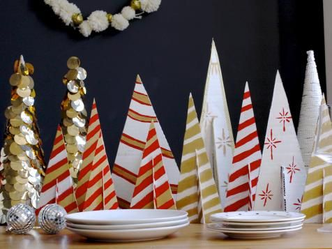 Cut balsa wood or even cardboard into two equal-sized triangles and put together to form a T. Boom: You have a tree for your centerpiece! Paint with craft paint in stripes, snowflakes or the design of you choice.