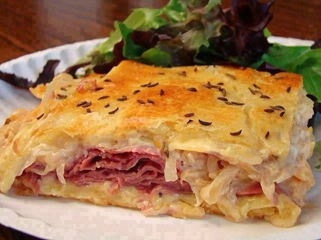 Reuben Bake 2 tubes cresc rolls 1 lb Swiss cheese 1-1/4 lbs sliced deli corned beef 14oz sauerkraut, rinsed&well drained 2/3C 1000 Island dressing 1 egg white  Press 1 tube on the bottom of a greased 13x 9 pan. Bake 375° for 8-10 min or until golden. Layer with 1/2 of the cheese & all the corned beef. Combine sauerkraut & dressing; spread over beef. Add remaining cheese.  Press or roll 2nd tube onto a 13x9 rectangle; place over cheese. Brush with egg white; sprinkle caraway seeds. Bake12-16…