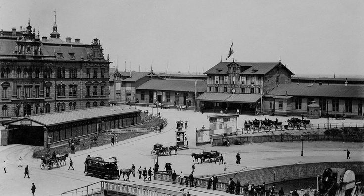Amsterdam, Droogbak. Links op nummer 1a het administratiegebouw van de Hollandsche IJzeren Spoorweg Maatschappij en ervoor de tramremise van de paardentram. Rechts het hulpstation Westerdok van de HIJSM (ca. september 1889).