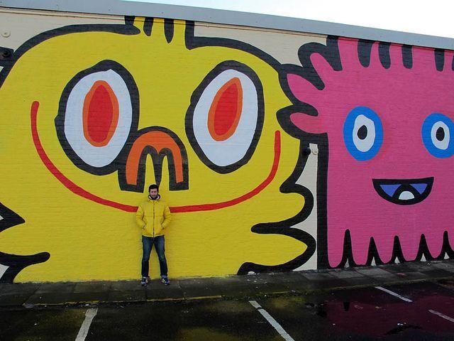 Jon Burgerman, next to his BIG character mural in Newcastle