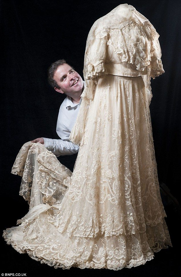 Auctioneer Phil Traves delicately arranges the 104 year old wedding dress which twice survived being bombed by the Luftwaffe during World War Two and will be auctioned on September 5