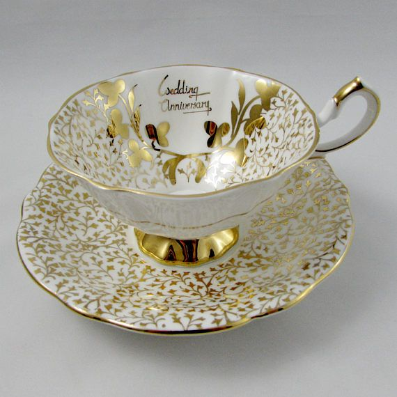 Vintage cup and saucer by Queen Anne, decorated with gold lace. Tea cup reads Wedding Anniversary. Perfect Anniversary gift! Queen Anne fine bone china tea cups and saucers were produced between 1911 and 1966 by Shore & Coggins. In excellent condition (see photos). Markings read: Queen