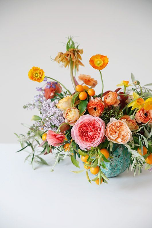 A colorful arrangement of garden roses, poppies, ranunculi, and kumquat branches | Tulipina More