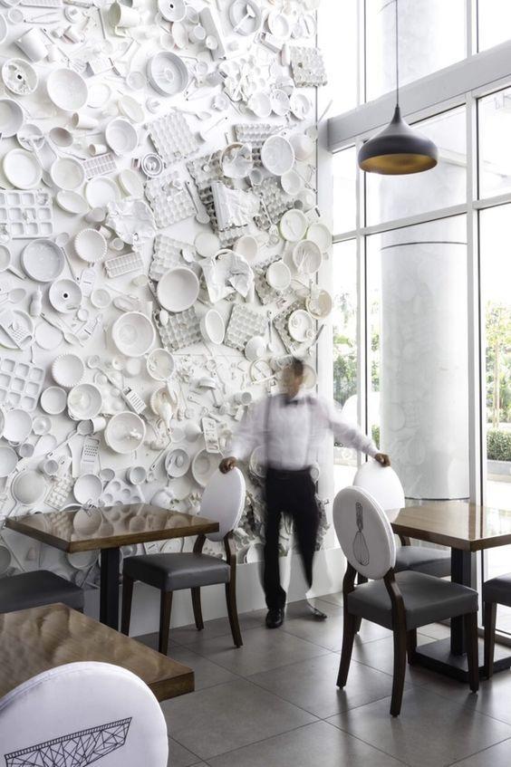 Pared de restaurante decorada con vajilla. Dyanon Bistro   Jannina Cabal   Archinect