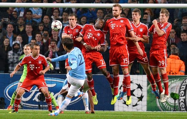 Manchester City's Spanish midfielder David Silva (3rd L) hits a free kick over the Bayern Munich wall during the UEFA Champions League group D football match between Manchester City and Bayern Munich at The City of Manchester stadium in Manchester, northwest England, on October 2, 2013.