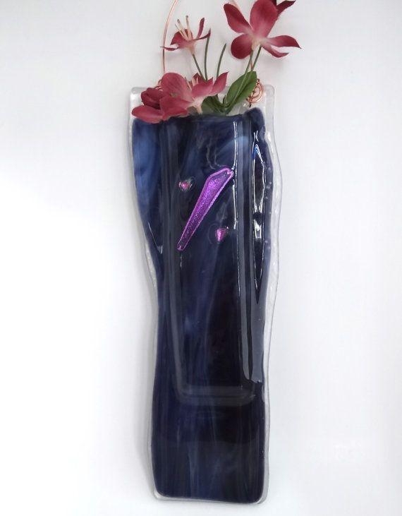 Μια τσέπη vased λιωμένο με μωβ διαφανές γυαλί και κρέμονται καλώδια χαλκού.
