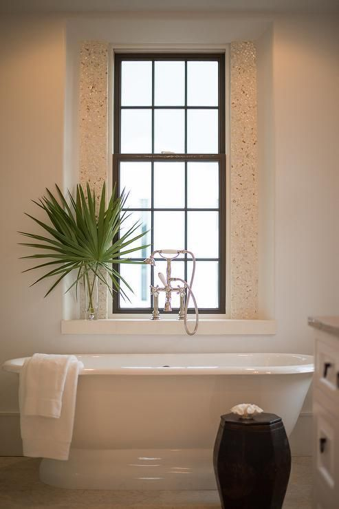 Coastal Bathroom Features A Roll Top Bathtub Placed Under A Window Nook Lined With A Vintage