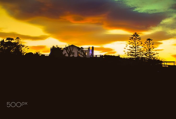 Silhouette Landscape - View of a house in the background at sunset.