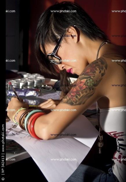 http://p1.pkcdn.com/kunstenaar-jonge-aziatische-vrouw-met-tatoeages-en-een-bril-op-het-werk_342413.jpg