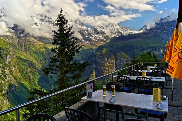 Hotel Edelweiss, Mürren, Switzerland  You're sitting: on the sun terrace   At: Hotel Edelweiss  Looking at: the big three of the Swiss Alps: Eiger, Mönch and Jungfrau Summits   Drinking: beer