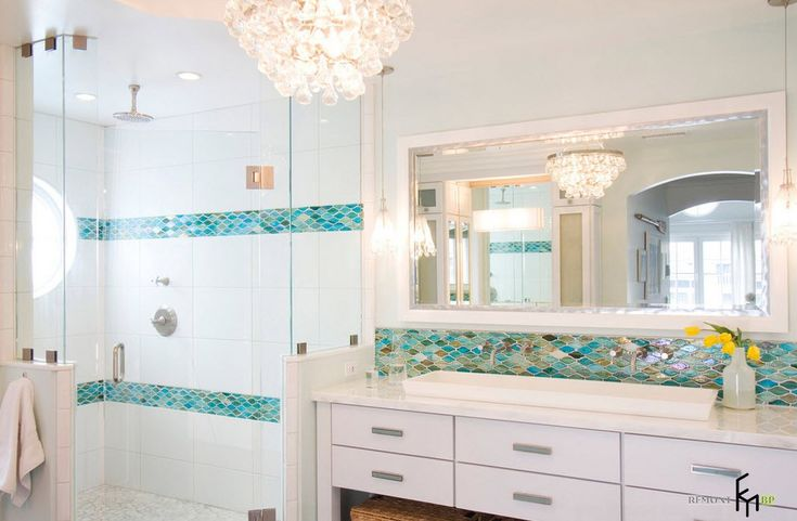 An awesome bathroom design with white marble and green mosaic backsplash with modern cabinet and sinks also frame mirror and lovely beaded chandelier