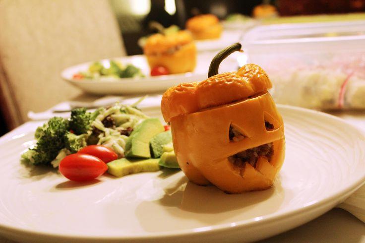 Pimentones rellenos con cara de calabaza y ensalada verde. Halloween