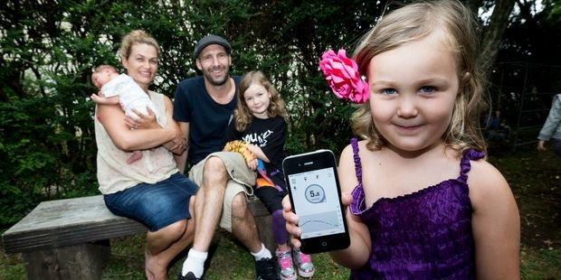 Gabrielle and Simon Hall with 2-week-old Stella, Mia, 8, and Georgia, 4, who shows off the smartphone tracking her glucose levels. Photo / Dean Purcell