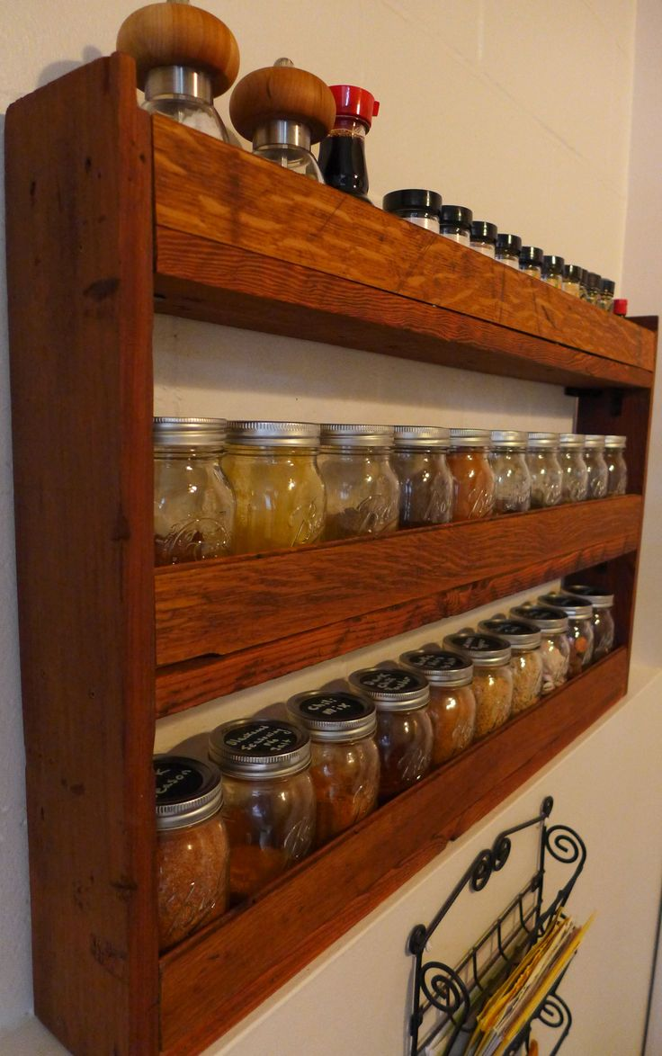 DIY spice rack for pint mason jars made from reclaimed wood: redwood sides, rough sawn fir shelves, and oak floorboards for the rails.