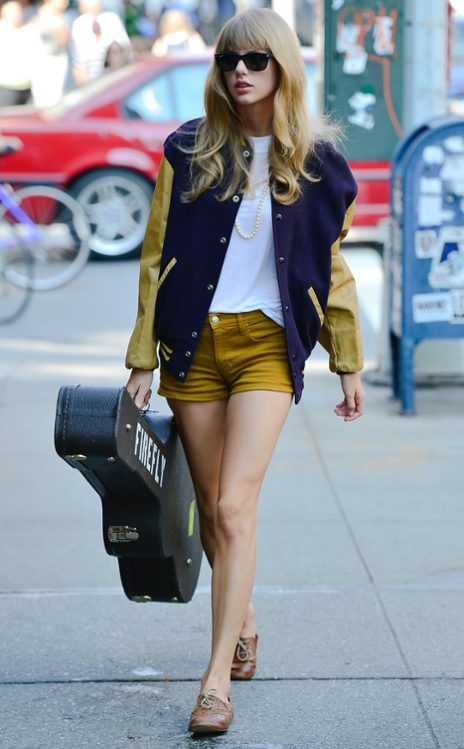 Taylor Swift wearing a yellow and blue varsity jacket, white t-shirt, and mustard yellow high waisted shorts.