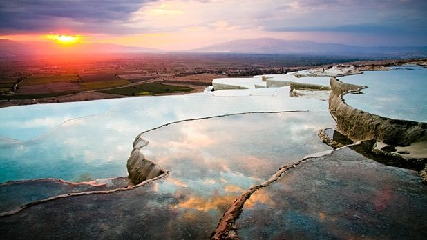 Pamukkale is an ivory mountain of terraced travertines (basins created by limestone-rich hot-springs) that has been used as a Roman spa since biblical times.