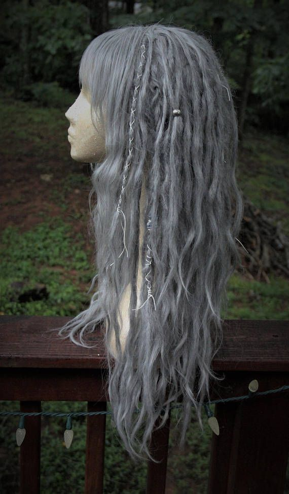 READY TO SHIP!!  One of a kind, will not be replicated!  This is a standard cap fair silver dreadlock wig with short, choppy, asymmetrical bangs and an assortment of decor including pure white wraps, silver beads, silver hair rings and thick braids. 27 in long layers layered, very full and natural  Bangs can be adjusted in length with placement of cap  Message me for any and all questions or comments!  ***** <3 Sarah  Wearing the hair in matted cords is an ancient tradition spanning the…