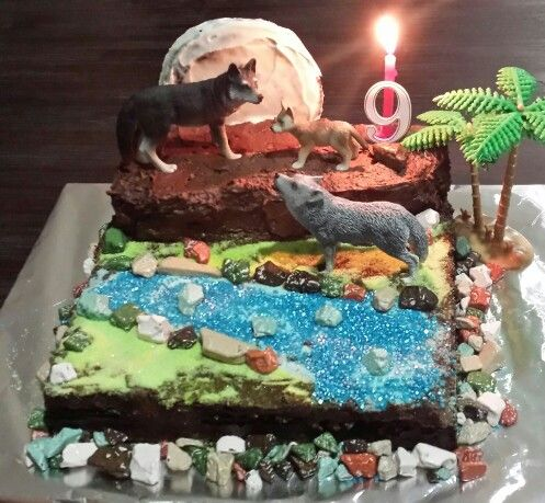 Amazing Wolf cake the cake is chocolate, the grass  water are jelly crystals, the rocks are choc rock  the moon is a cookie with icing suger to give it the moon look. Wolves and  trees are from the toy shop.
