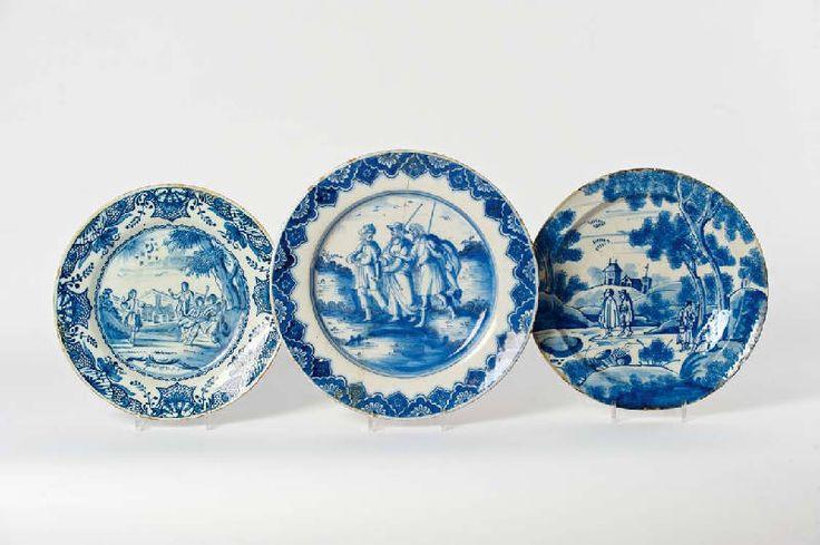 Drie diverse Delfts blauw aardewerk ronde schotels  18e eeuw, ��n gemerkt De Porceleyne Lampetkan een met een centraal bijbels decor, Genesis 37:1-9 (LPK), een met een bijbelse voorstelling, deze twee met florale ornamentbanden, de derde met een vol decor van figuren in een landschap met een dorp op de achtergrond (beschadigingen, restauraties). (3) D 33,5, 38 en 35 cm