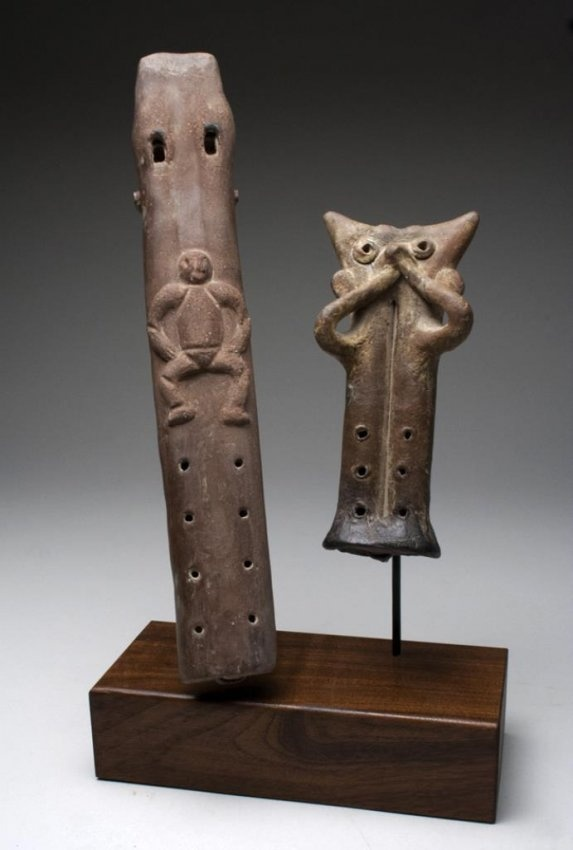 """*Pair Of West Mexican Colima Pottery Flutes : Pre-Columbian, West Mexico , 500 BCE – 500 CE. Set of two Double Flutes - one with a Human Figure in Relief, the other with a Mask-Like Face Holding two Hands to its mouth like a Flute Player. 12""""T x 2""""W."""