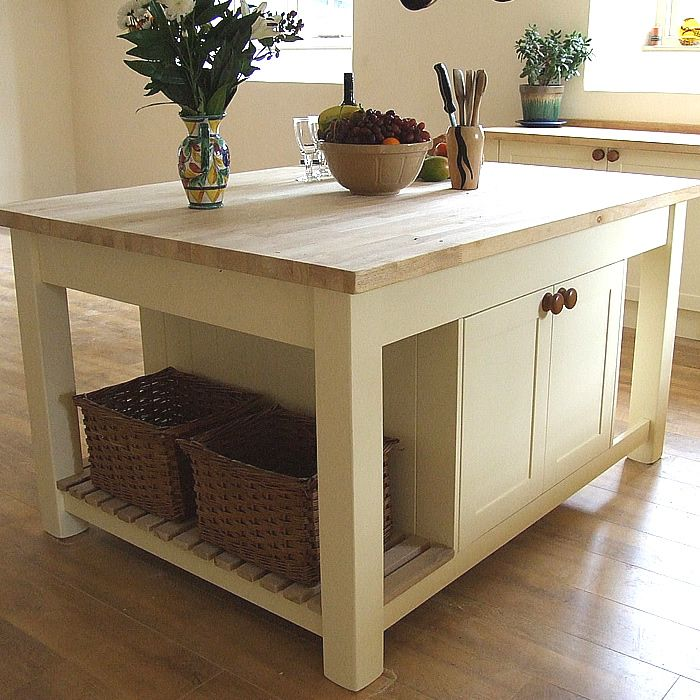 Freestanding kitchen island incorporating 2 back-to back 800mm wide cupboards, slatted end shelf & breakfast bar end area. Painted underframe with Danish oiled, beech top, size shown L:1400mm W:1200mm H:910mm Shown here finished in Dulux Heritage Cream, any size or configuration and colour can be made to order. See more here http://colinspicer.co.uk/painted-shaker-kitchens-wales