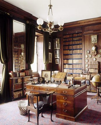 The Library at Erddig with the C18th mahogany library table (in the manner of Thomas Chippendale), desk chair, and corner view of floor to ceiling bookshelves and large mirror on one wall.