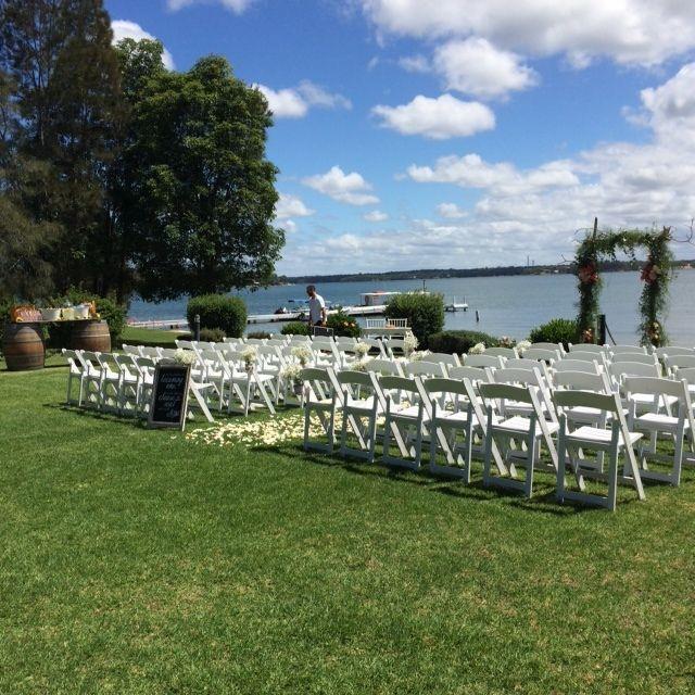 Sarah's #stunning #wedding @Raffertysresort #rusticArch #whitefoldingchairs #babysbreath #masonjars #rosepetals