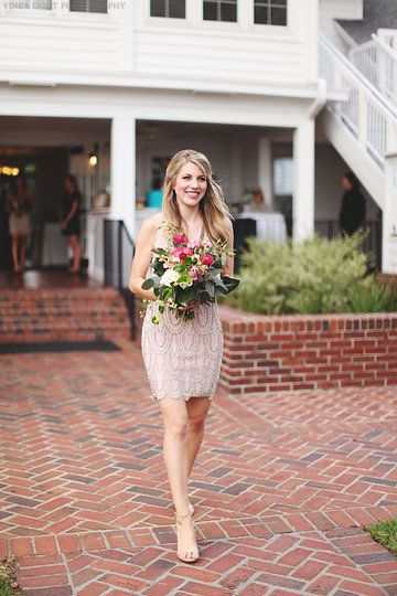 dressed in a neutral blush dress, the bridesmaid carries her loose unstructured bouquet of coral charm peony, red ranunculus, Vendala roses, hot pink ranunculus, light pink lisianthus, jasmine vine, magnolia leaves, lemon leaf, peach stock, succulents & seeded eucalyptus wrapped in cream muslin ribbon.
