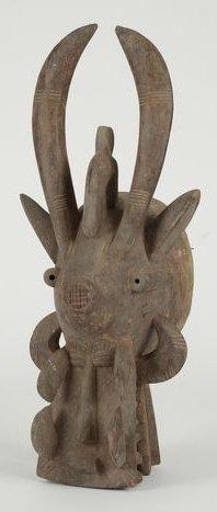 """Masque heaume dit """"cracheur de feu"""", il représente un animal mythologique composite et est utilisé par la société secrète Senoufo du Poro. Patine brun clair. Haut.: 73 cm"""