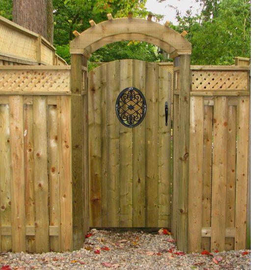 Custom wood fence and gate with metal decal. Custom wood pergola over gate