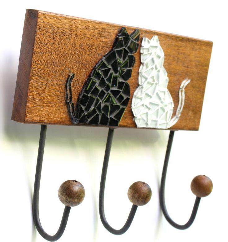 Um charmoso casal de gatinhos enfeitam esse cabideiro em madeira de lei, com mosaico feito em pastilhas de vidro. Ideal para organizar bolsas, roupas, capas de chuvas, toalhas ou ainda na cozinha, decorando e auxiliando na organização de guardanapos... <br>Vem com três ganchos em ferro tratado e pintado, com bolinhas de madeira na ponta. E dois ganchos atrás, para uma perfeita fixação na parede. <br> <br>Tamanho: 21 cm de largura x 19 cm de comprimento