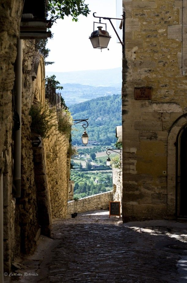 Gordes, France — by Carlotta Rebonato. Almost white stone houses with light blue balcony, breath taking view from each alley, panoramic roads all around and...