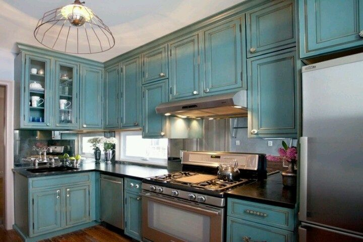 this eclectic l shaped kitchen layout features teal cabinets with a