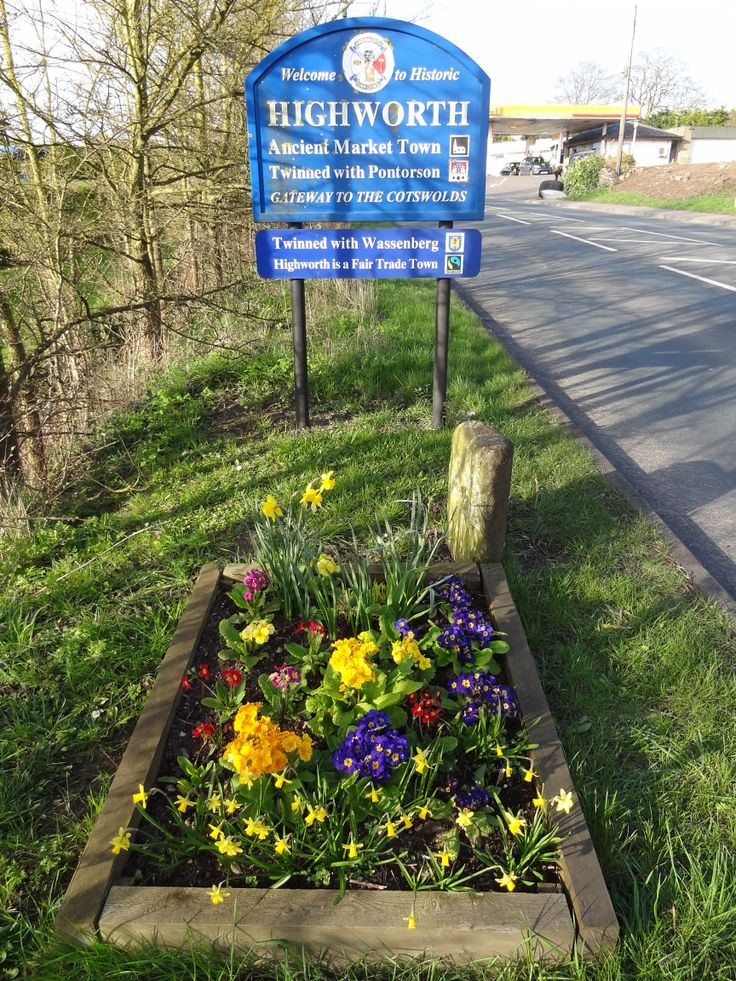 Welcome to Highworth sign with spring garden (March 2014), Ancient Market Town. Twinned with Pontorsom and Wassenberg. Highworth is a fair trade town and gateway to the Cotswolds.