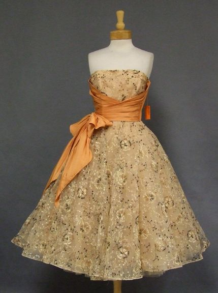 Dress, 1950's, of buff colored tulle with pleated apricot acetate on the bust and a large pleated apricot acetate bow at the right side.