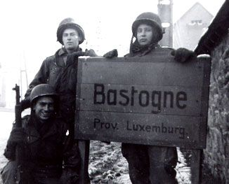 December, 1944, three members of Division Signal Company, 101st Airborne Division pose with another of the town signs, on the road coming-in from the northwest perimeter. This was taken right across the street from the Belgian Army barracks', where General McAuliffe established his divisional C.P. and where he made the classic 'Nuts' reply to the German demand for surrender. The stone wall at right is the edge of the town cemetery, and a comparison of this shot can still be made.