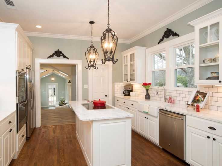 As seen on HGTV's Fixer Upper, this gorgeous cottage kitchen features refinished hardwood floors, white cabinets, a subway tile backsplash and a pretty light blue paint job. Ornate metal chandeliers illuminate a large kitchen island with plenty of storage and a new granite countertop.