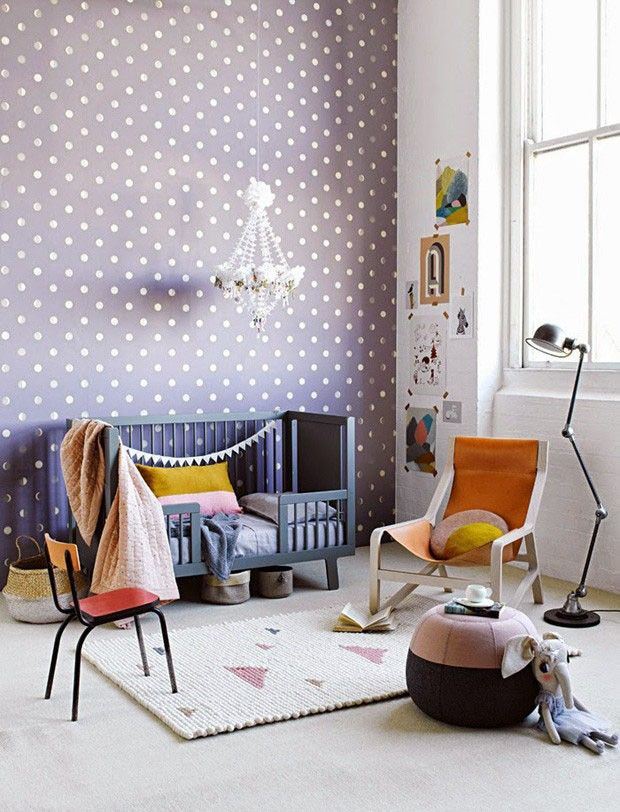 Papel de parede de bolinhas e berço numa cartela refrescante de roxos e lilases dividem espaço com móveis de design, criando um espaço descontraído e lúdico.