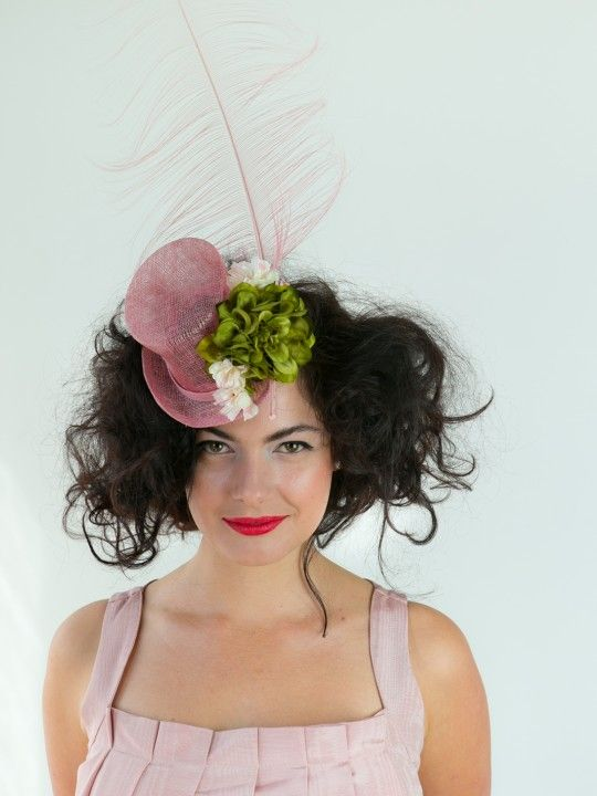 PRETTY HATTER   Pink Top-Hat/Fascinator for Spring Racing Carnival   FORD MILLINERY  $315    Why is a raven like a writing desk? When you look this pretty, who cares?! Her dusty pink sinamay mini top-hat is adorned with a gorgeous moss green silk flower, and silk cherry- blossoms to boot. The show-stealer is the regal dusty pink burned ostrich feather plume. A little more tea? Go mad, Pretty Hatter.    Colour & material of trim (flowers, feathers etc.) may vary depending on base colour…