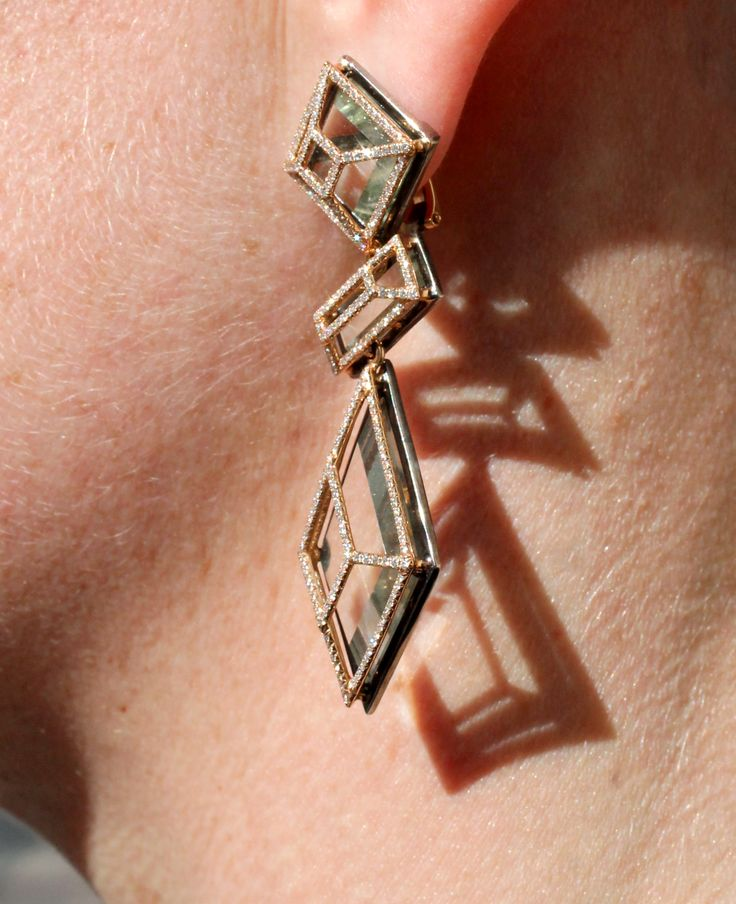 AENEA Facette earrings with green amethyst, set in yellow gold with diamonds. Very geometric fashion statement. With shadow behind. Photo in Salzburg, Austria in Europe. Street style inspiration. http://www.thejewelleryeditor.com/jewellery/article/aenea-jewellery-austria-salzburg/ #jewelry