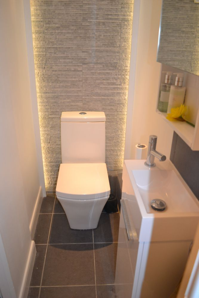 Lighting around toilet with a gold backsplash