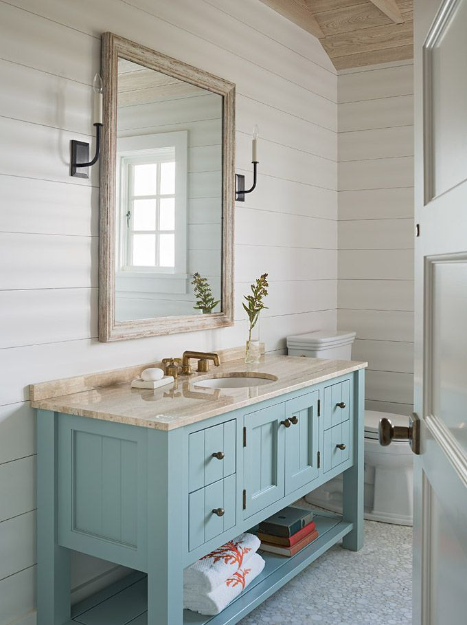 This is the perfect summer house bathroom with shiplap walls, a weathered wooden mirror with sconces and a painted blue-green vanity