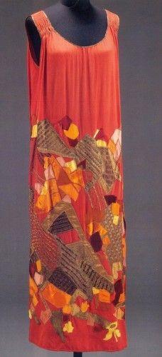 Evening dress of multi-coloured silk and velvet appliqué on red silk. Designed by Natalia Goncharova for Maison Mybor, Paris, about 1923, V&A