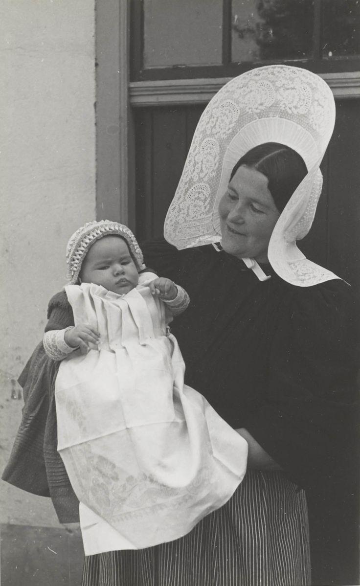The Netherlands, Huizen. Moeder met baby in Huizer dracht De moeder is gekleed in hedendaagse dracht (anno 1945). De baby is gekleed in een reconstructie van de oudere doopdracht (circa 1920). Het draagt een doopmutsje en een lichtblauw doopjurkje met daarover een geplooid servet. #NoordHolland #Huizen #isabee